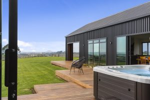 A rural property that has new cladding, a new roof, and a new deck and with a large front lawn