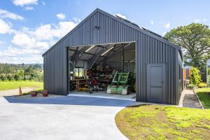 The exterior of a large outdoor workshop set in the countryside, with impressive new cladding and roof