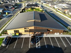 An aerial photo from distance of a commercial building with a new roof and with car parks in front
