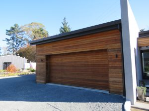 A large garage door with wooden panels and a new roof on the home